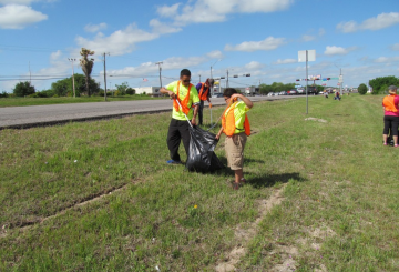 alumni working together to clean up highway litter