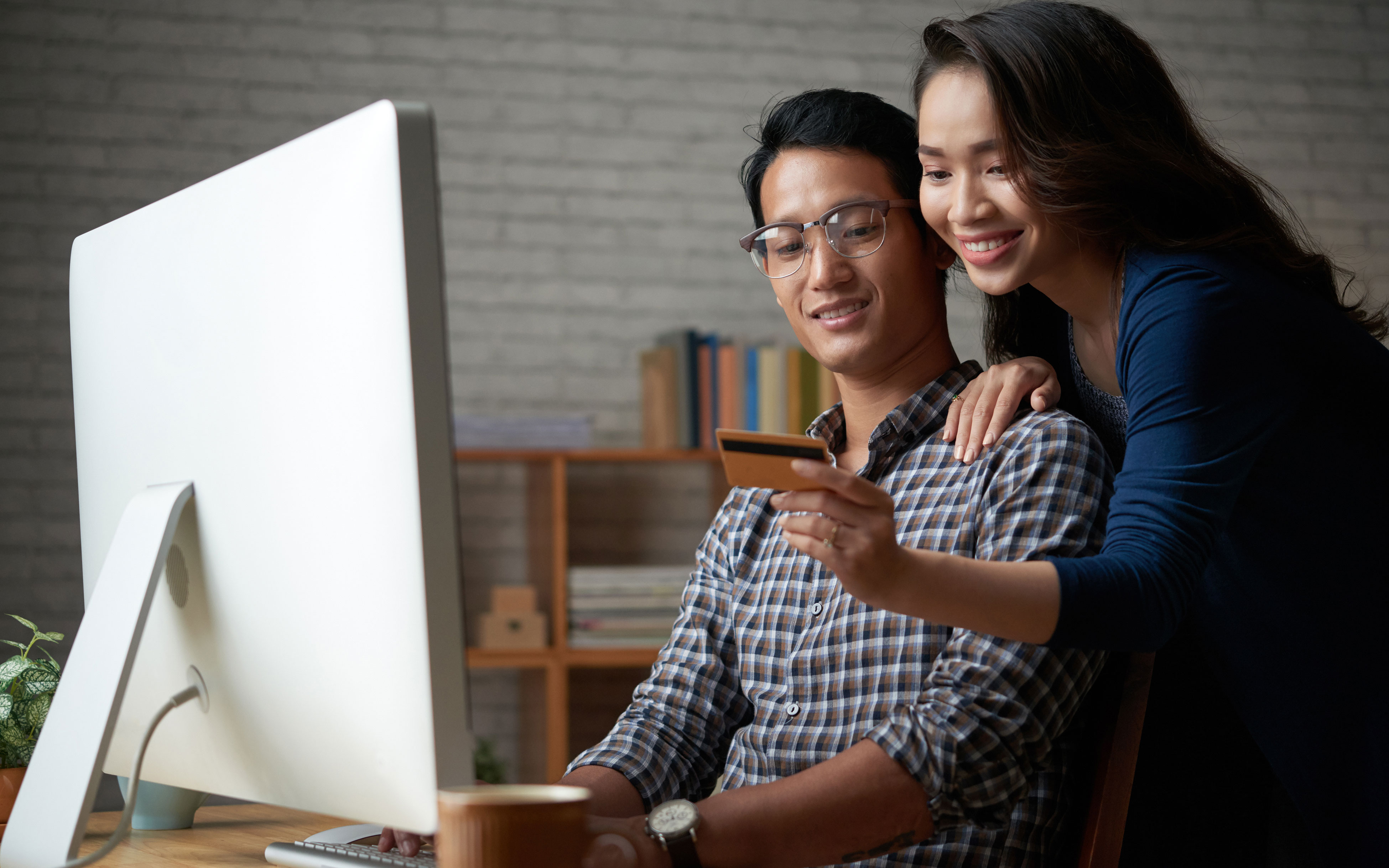 female leaning over male shoulder to give credit card numbers, both in front of computer