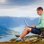 student on top of a mountain with laptop