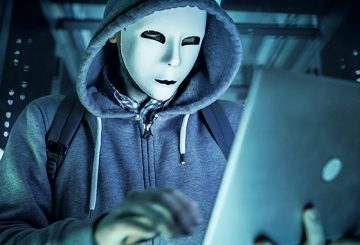 man wearing mask in a hoodie on laptop