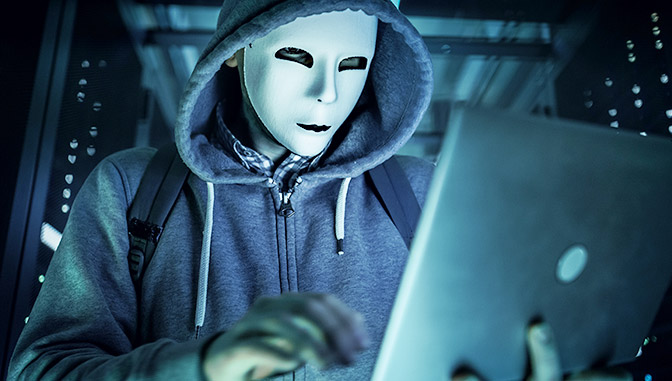 man wearing mask in a hoodie on laptop