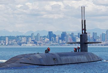 submarine emerging from the water in front of a city