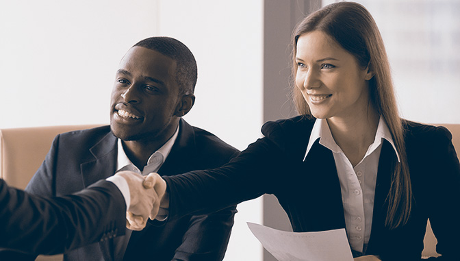 women and african american man in suits shaking hands