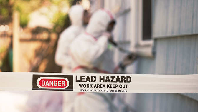 danger tape for lead hazard and workers in white hazmat suits