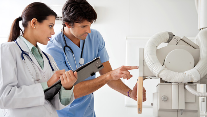 female doctor and male nurse reading results on medical equiptment