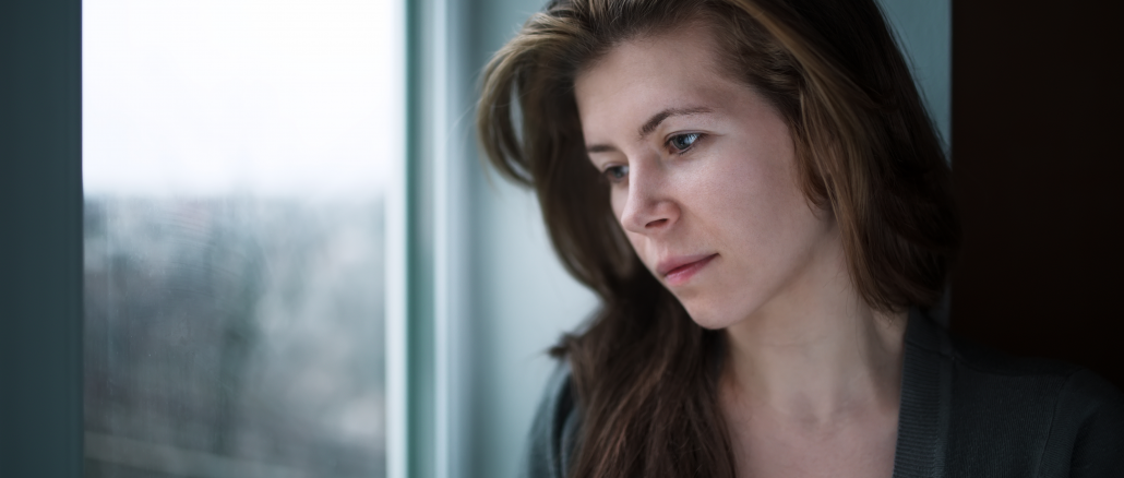 depressed woman staring blankly out the window