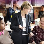 three professional women laughing