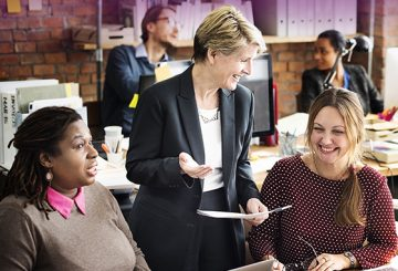 three professional women laughing