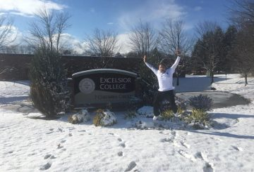 Andrew Lieberam jumping for joy in front of Excelsior College sign