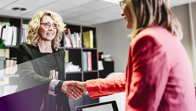 two professional women shaking hands, negotiating salary