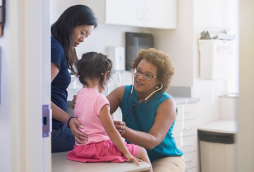 african american nurse doing a check up on a young asian girl and her mother