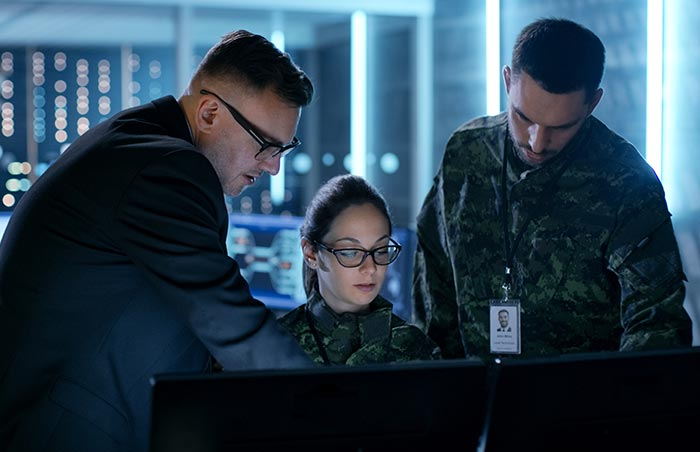 Military leadership group working on a computer