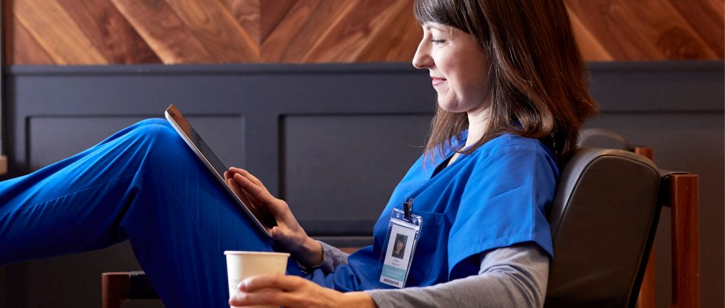 female nurse in scrubs practicing self care, drinking coffee