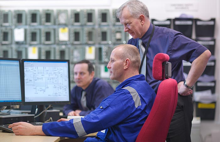 Nuclear power plant engineers consulting with each other.