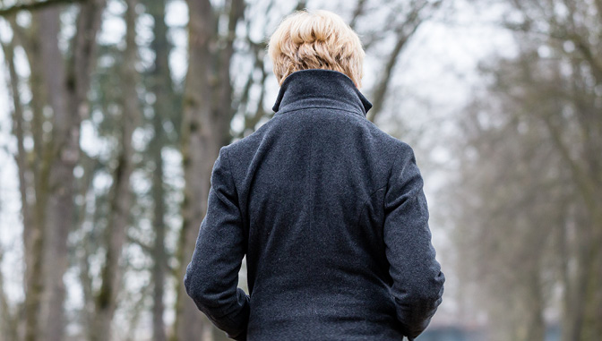 Woman with back turned in winter, suffering from Seasonal Affective Disorder
