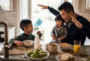 asian father and two sons playing at a table