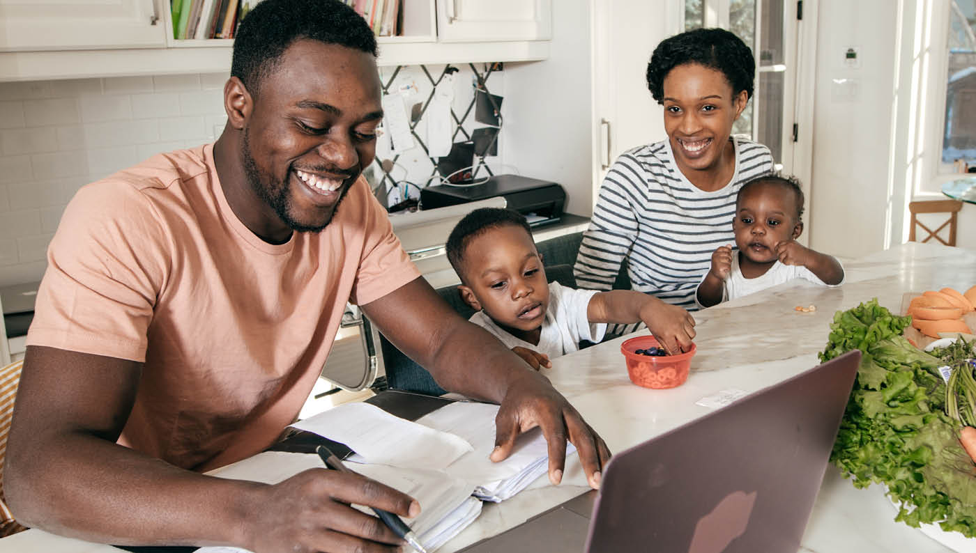 African American Man on Laptop surrounded by wife and kids