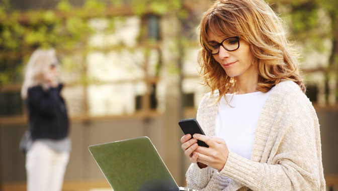 caucasian woman using laptop and smartphone to study