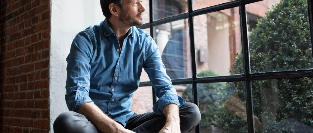 man contemplating an online masters degree out a window