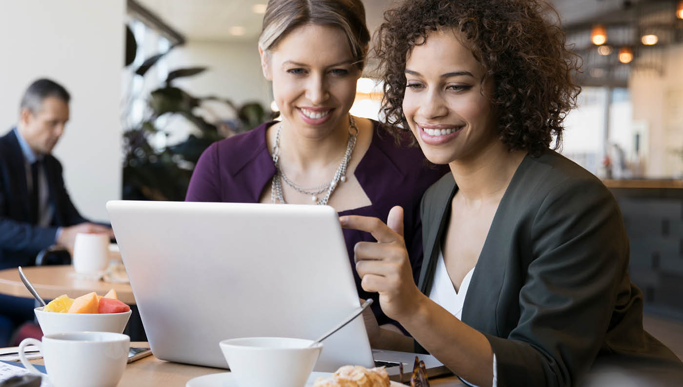 two women looking at a laptop