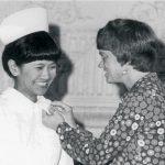 Carrie B. Lenburg putting a pin on a nursing graduate