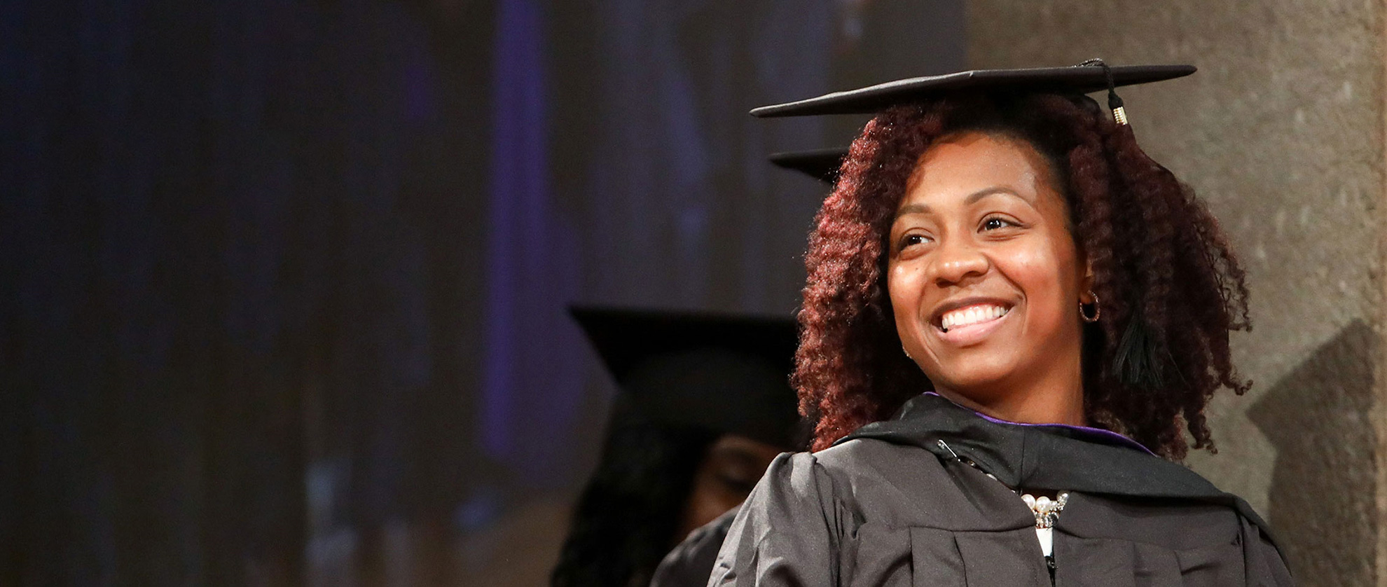 Excelsior College Graduate Smiling at Commencement Ceremony